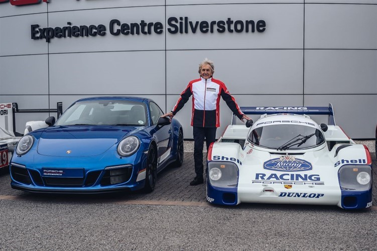 Derek Bell standing with two Porsche super cars at Sherborne Castle