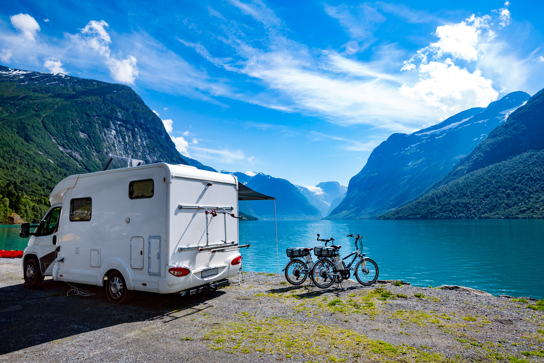 A motorhome parked on the edge of a blue lake in a mountainous region with bikes outside of the motorhome