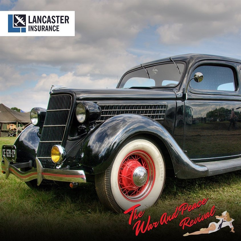 Black classic car with white wall tyres at show with Lancaster Insurance and The War and Peace Revival logos around it