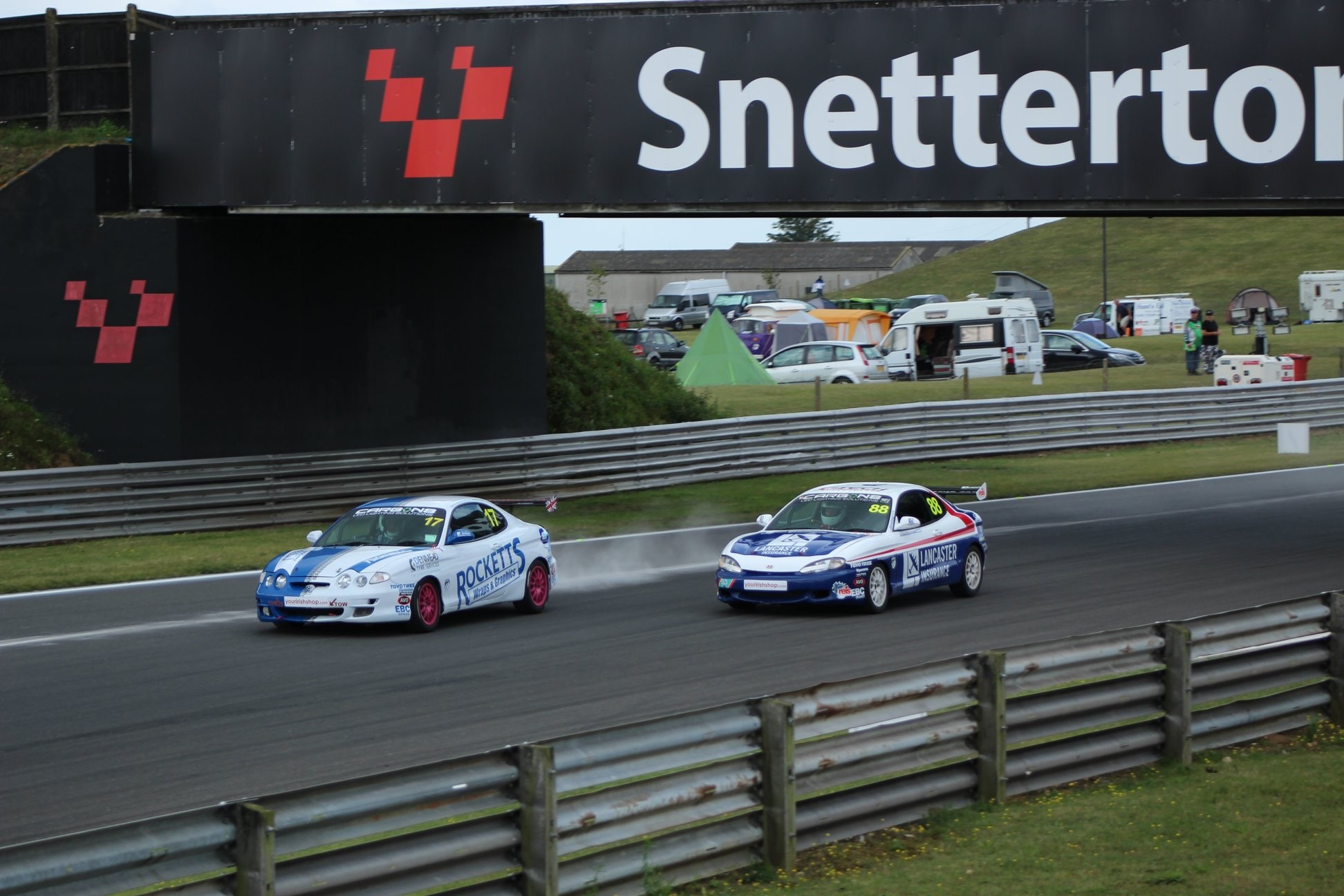 Alex attacking Wayne Rockett for the lead going into the esses