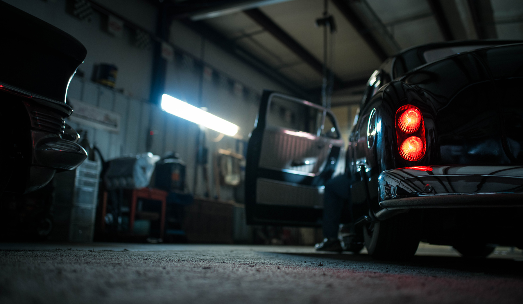 A classic car idling in a dimly lit garage with the owner working on restoring it