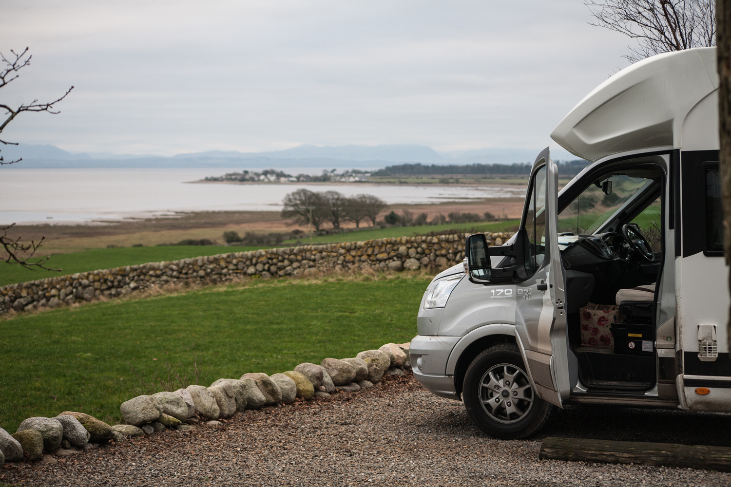 A motorhome with its door open parked in a gravel car park next to a large lake
