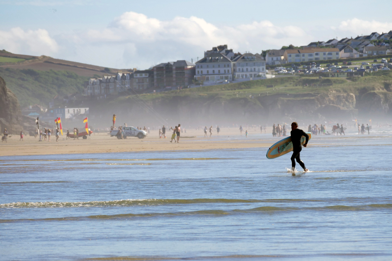 A person surfing on the sea in-front of a busy sandy beach in Cornwall