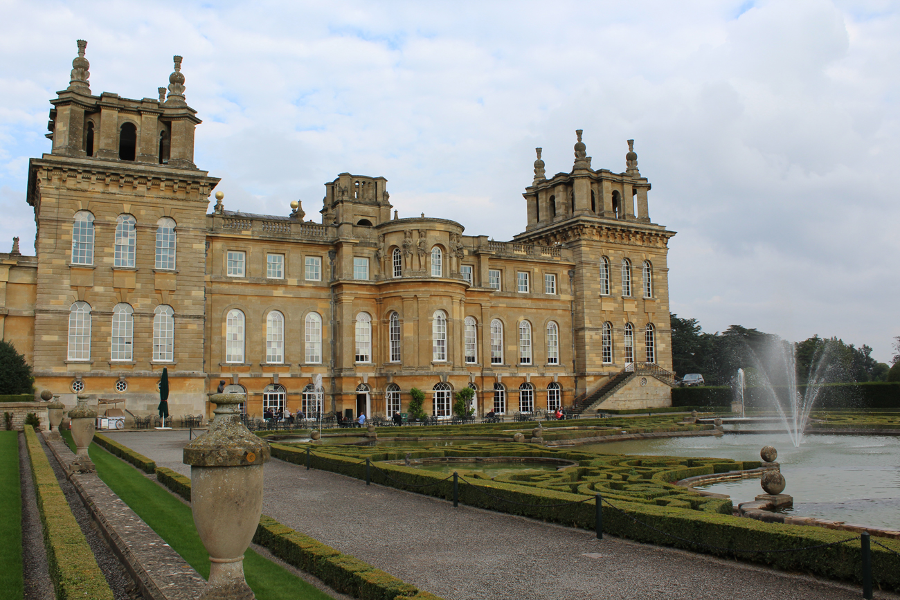A large stone building with well kept gardens and a fountain in-front at Blenheim Palace