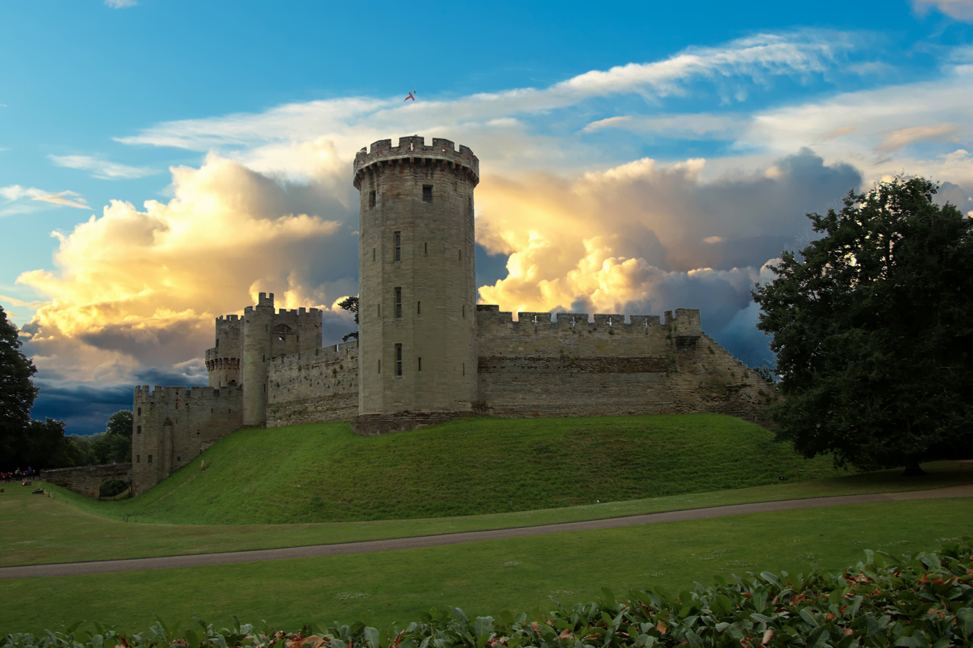 Warwick castle with thick clouds in the distance at sunset