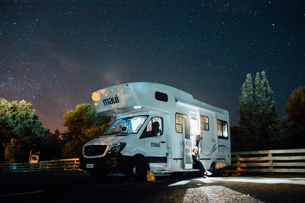 A motorhome parked at a campsite under a starry sky