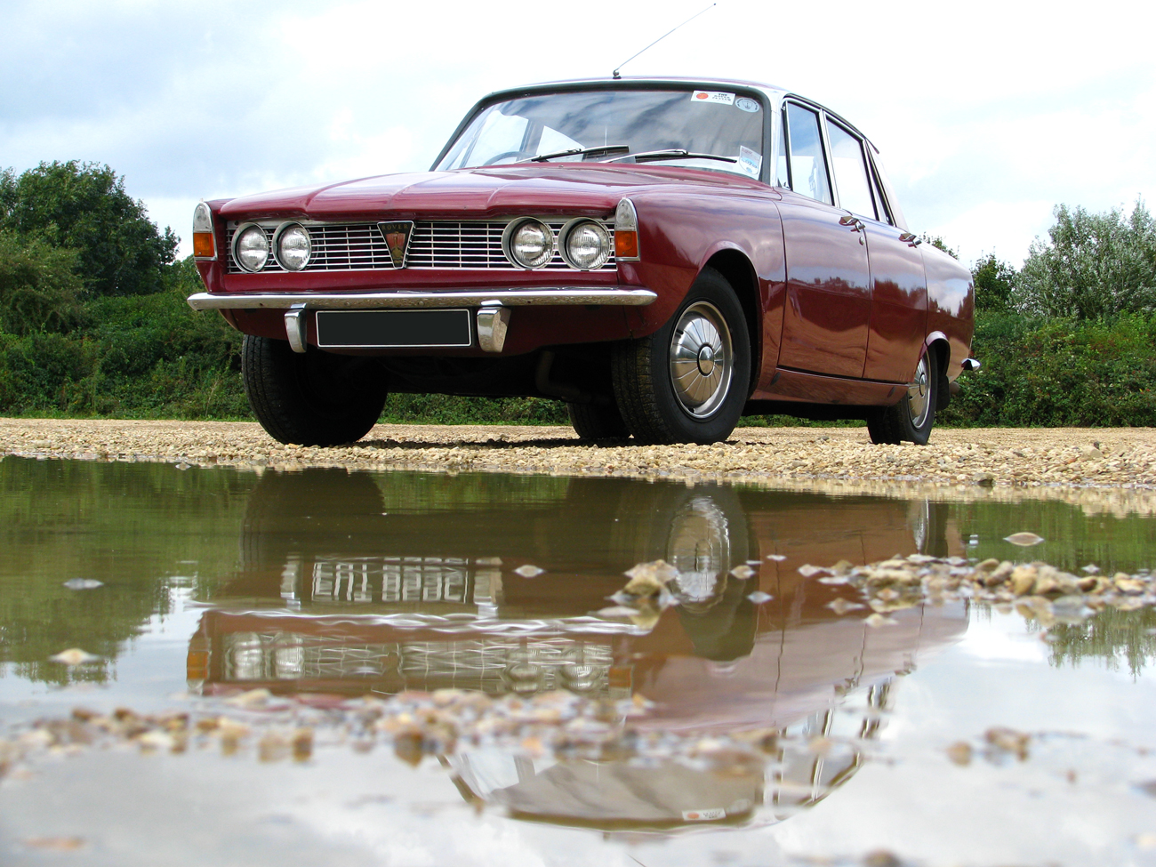 A Rover P6 2000 parked in-front of a large puddle