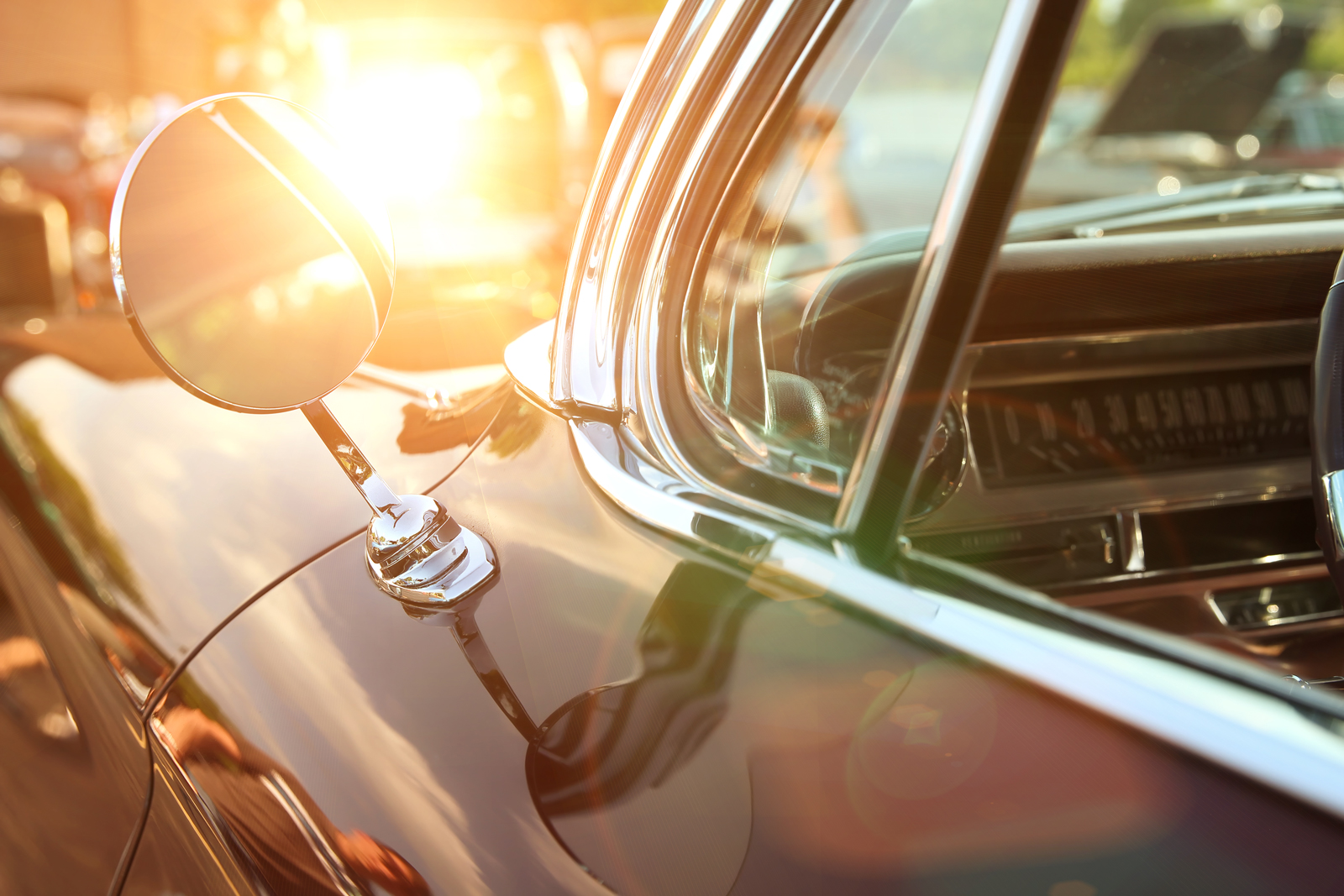 Light shining behind the wing mirror of a classic car