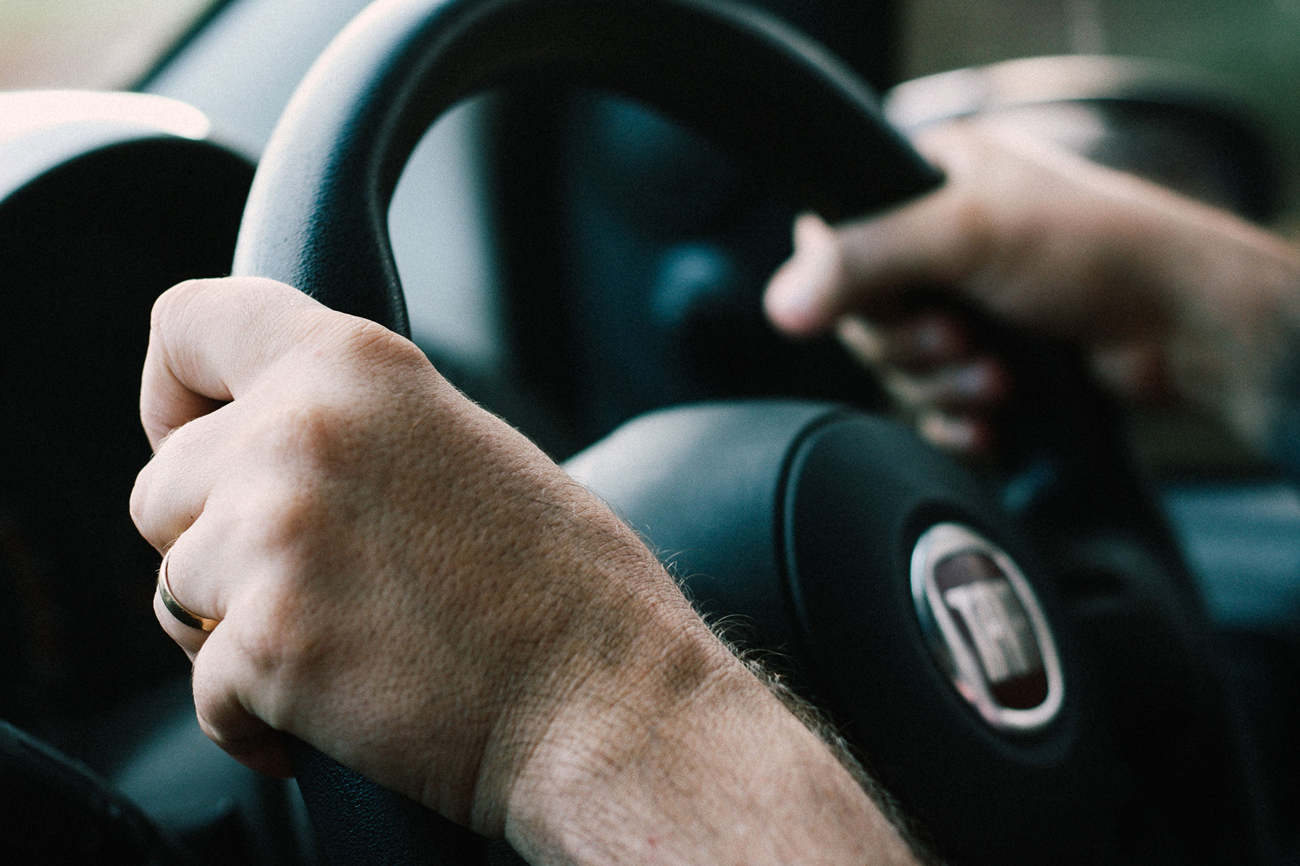A person with two hands on their steering wheel