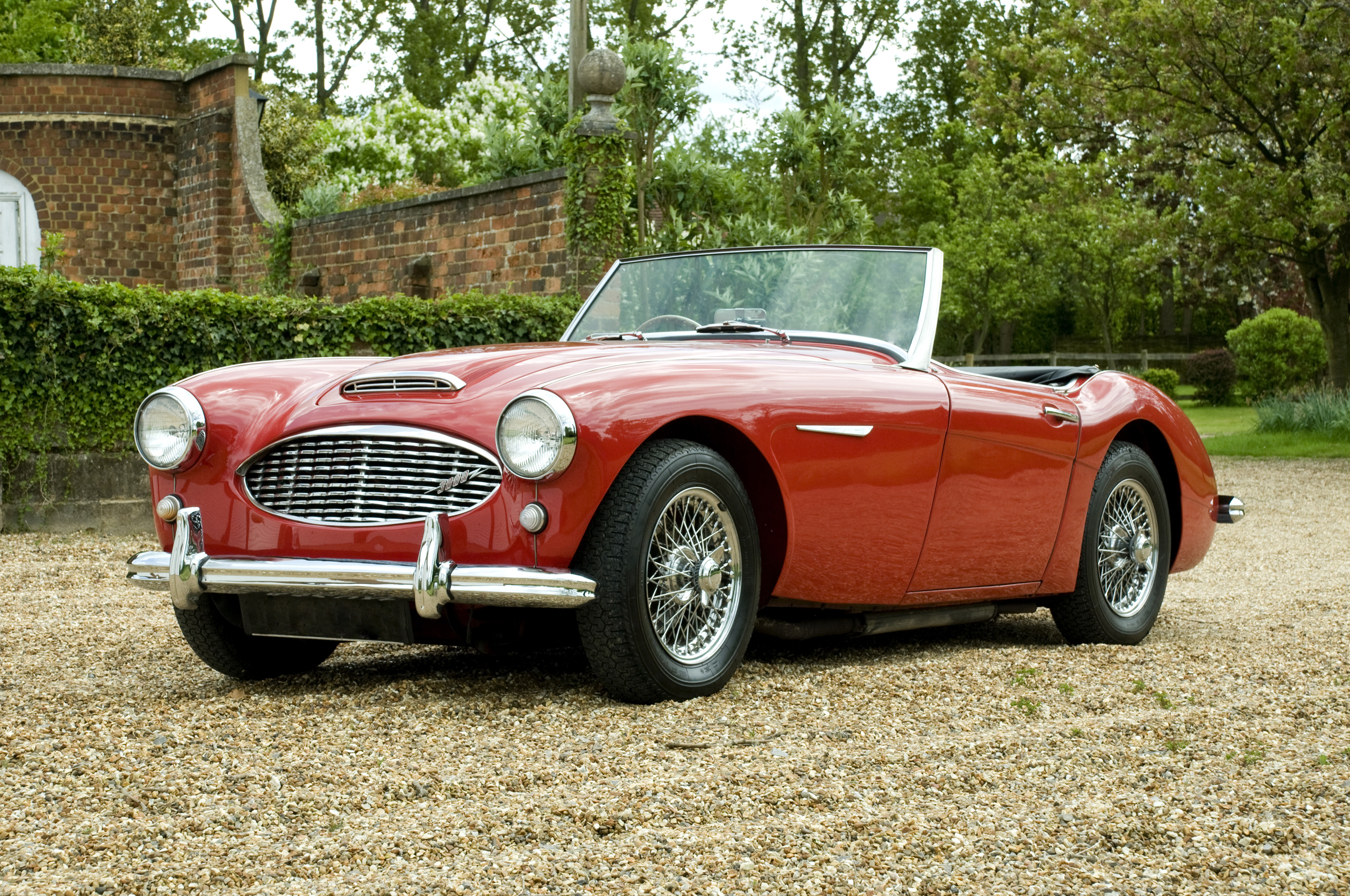 A convertible red Austin Healey parked on a gravel driveway