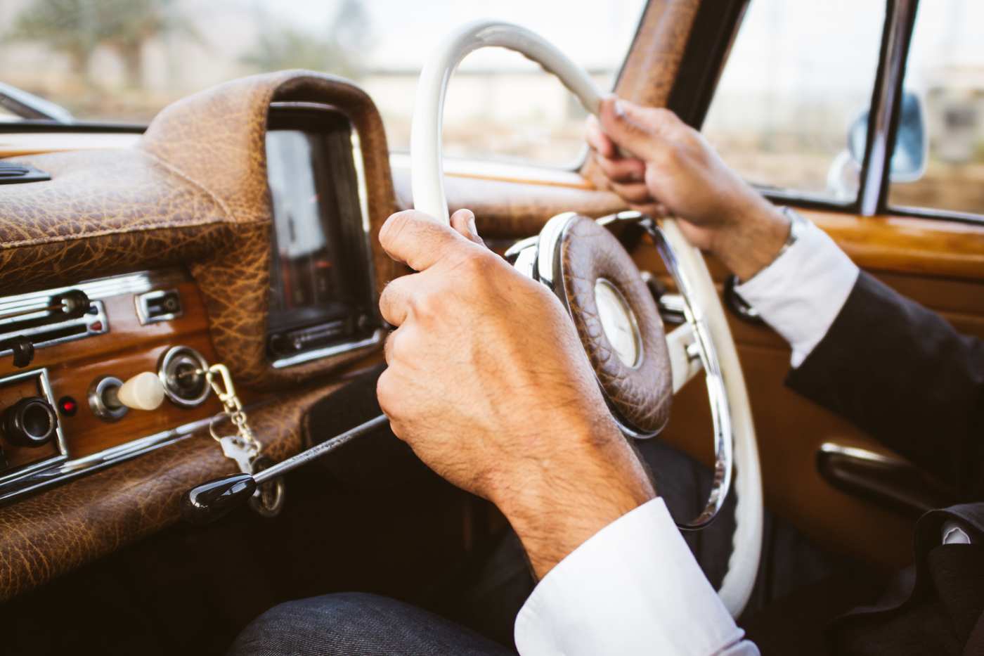 A man in a suit driving a classic car