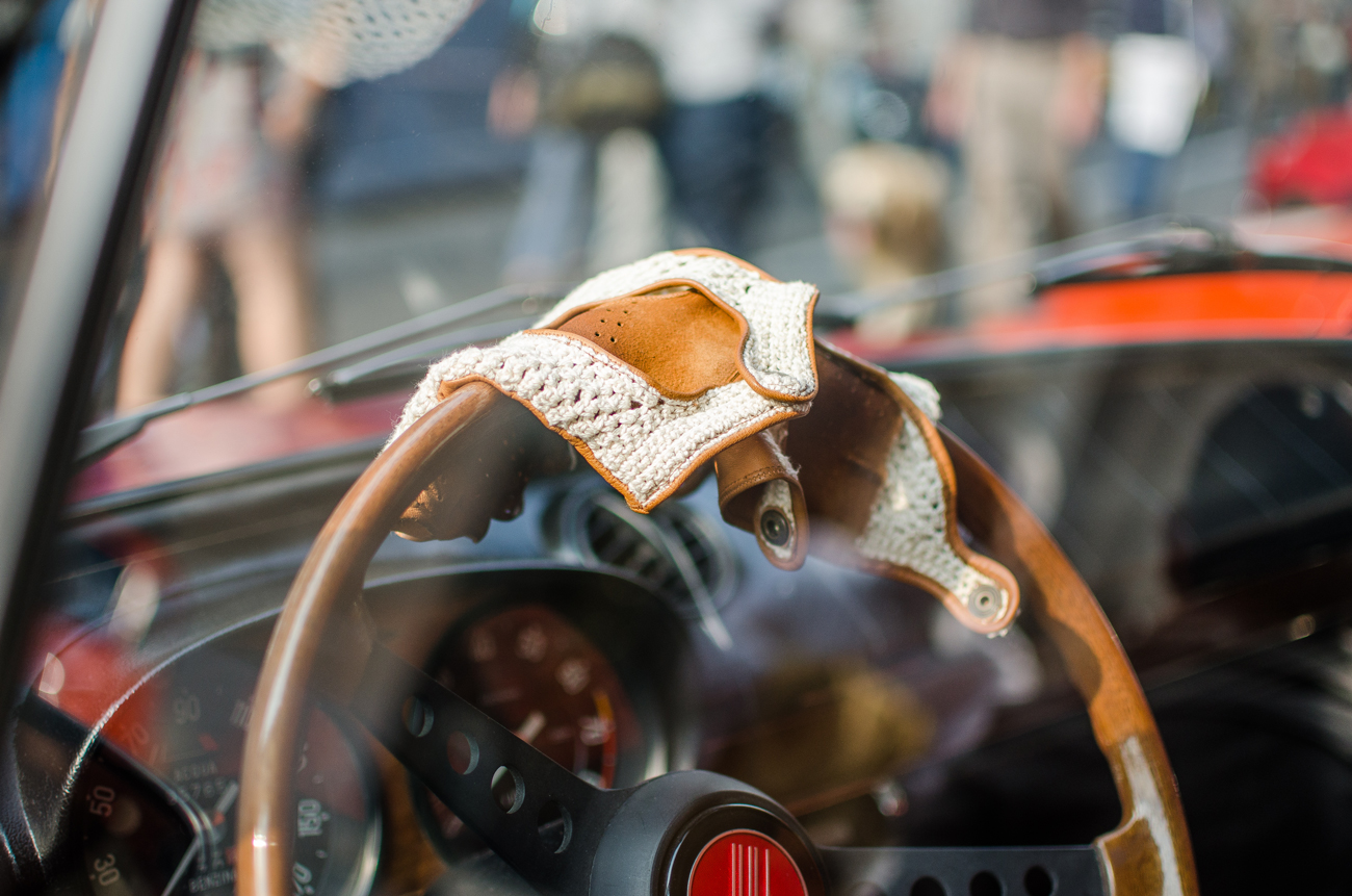 A pair of leather driving gloves placed on a wooden steering wheel in a classic car
