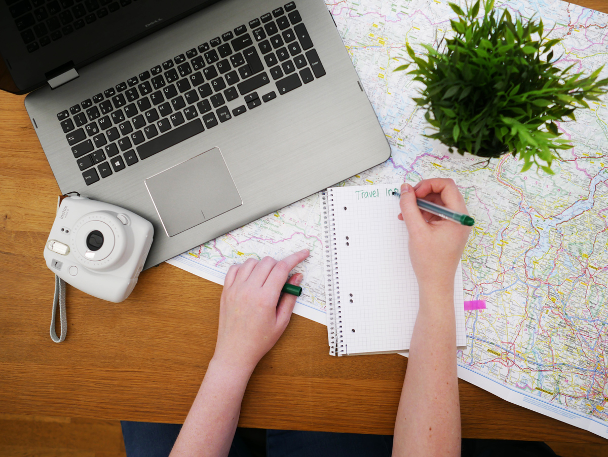 A person writing a travel plan on a notepad next to a laptop, a Polaroid camera and a map