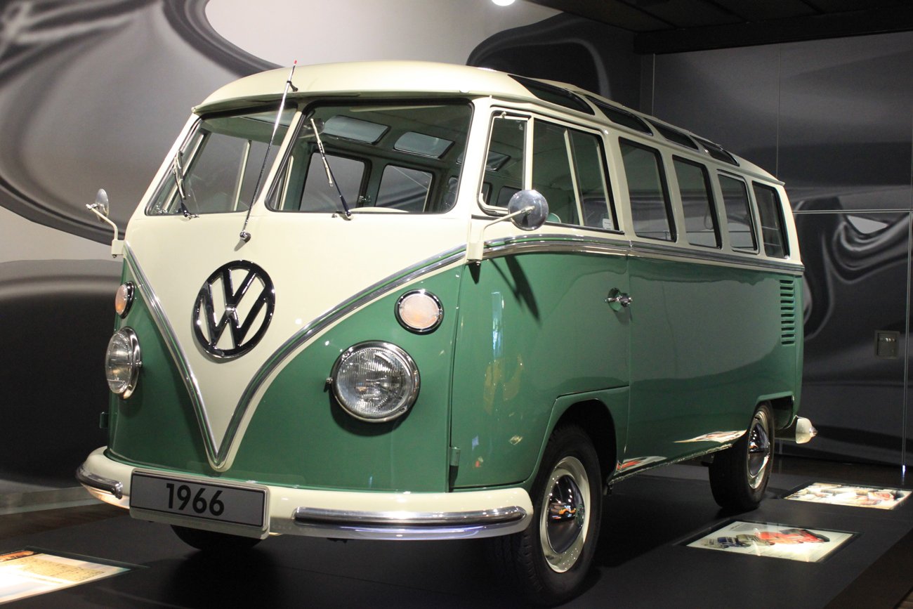 A green and white 1966 Volkswagen T1 Transporter in a museum exhibit