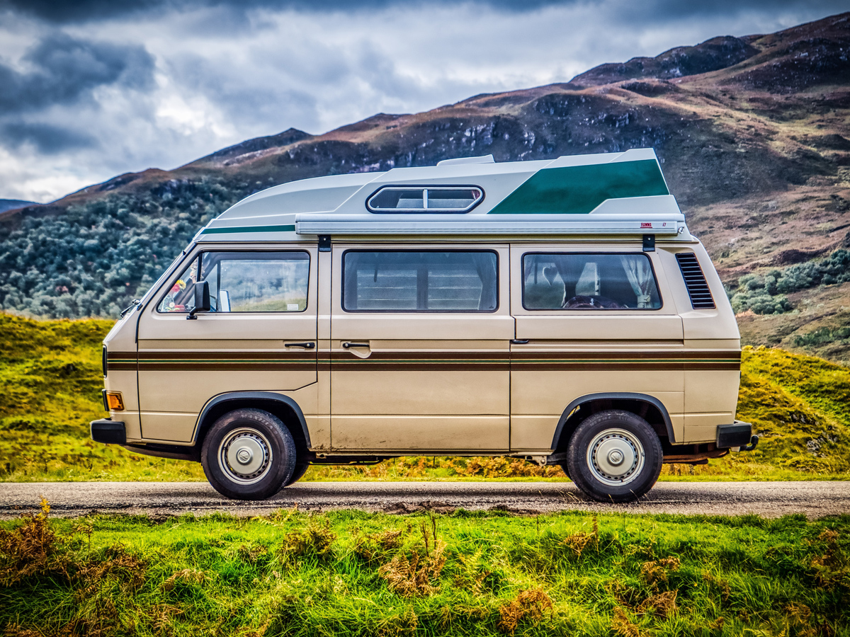 A Volkswagen T25 Transporter on a road in the green highlands of Scotland