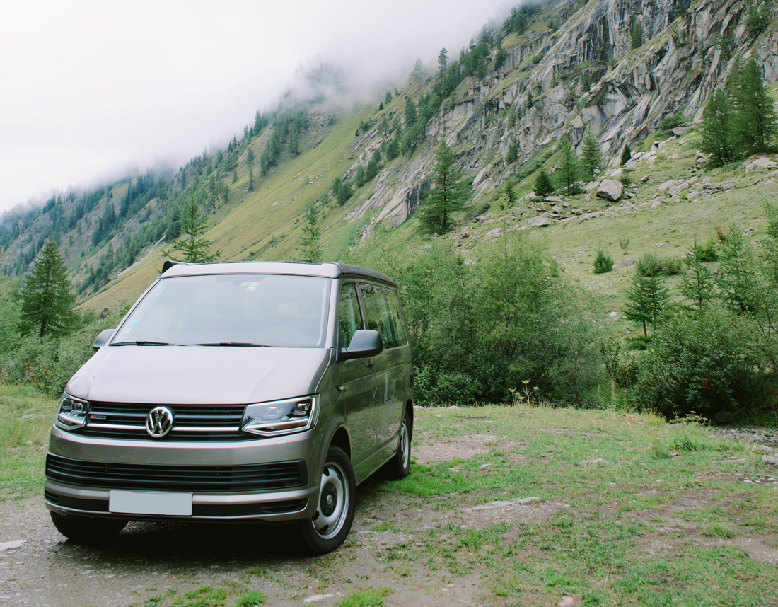 A brown Volkswagen T6 Transporter parked on a grassy hillside in an alpine region