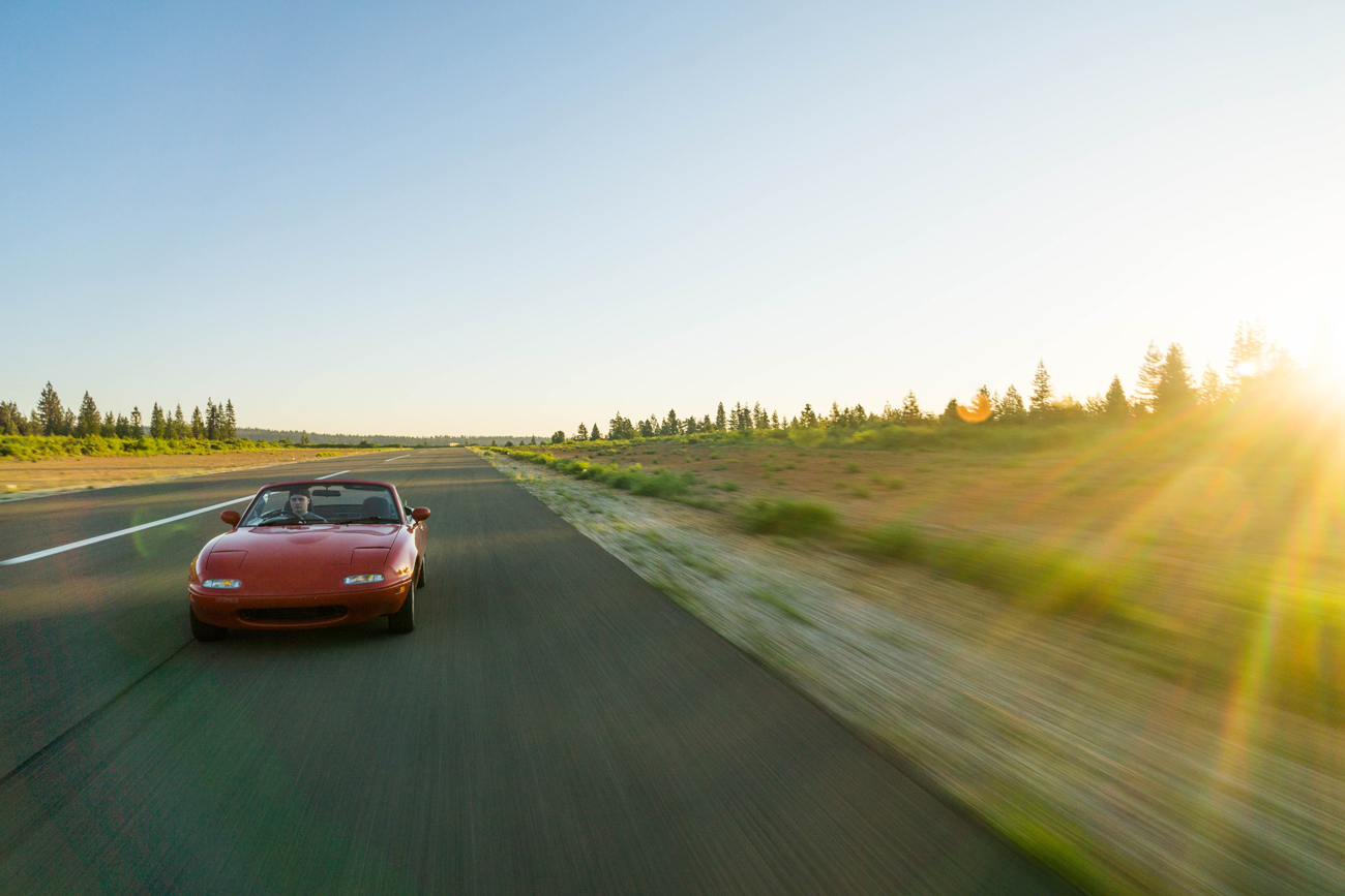 A Mazda MX5 driving at speed on an open road with the sun setting off to one side