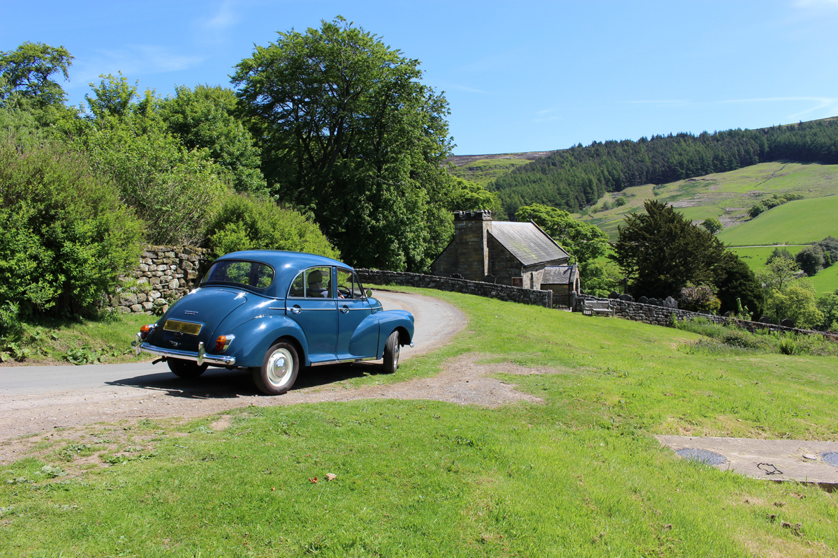 A Morris Minor driving on a country road next to an old farm with green rolling hills and woodlands in the distance#