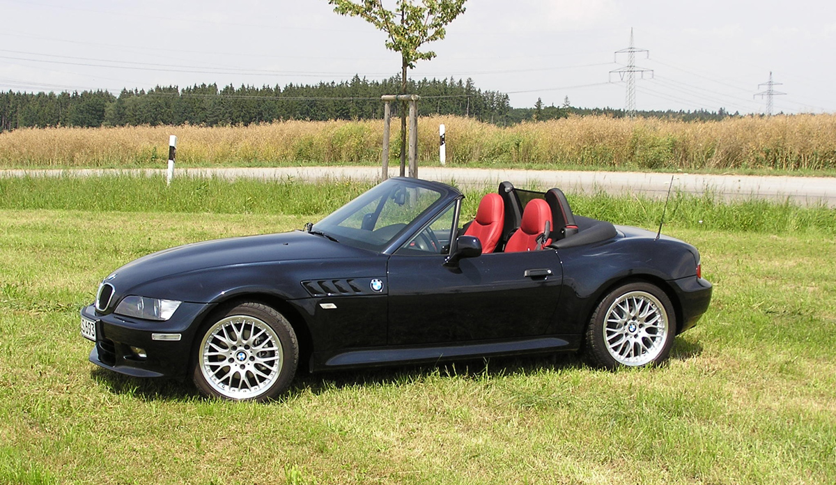 A black BMW Z3 parked on a field with the roof down on a sunny day