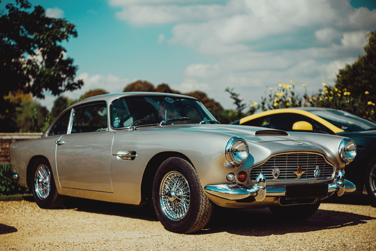 An Aston Martin DB5 parked in a gravel car park on a sunny day