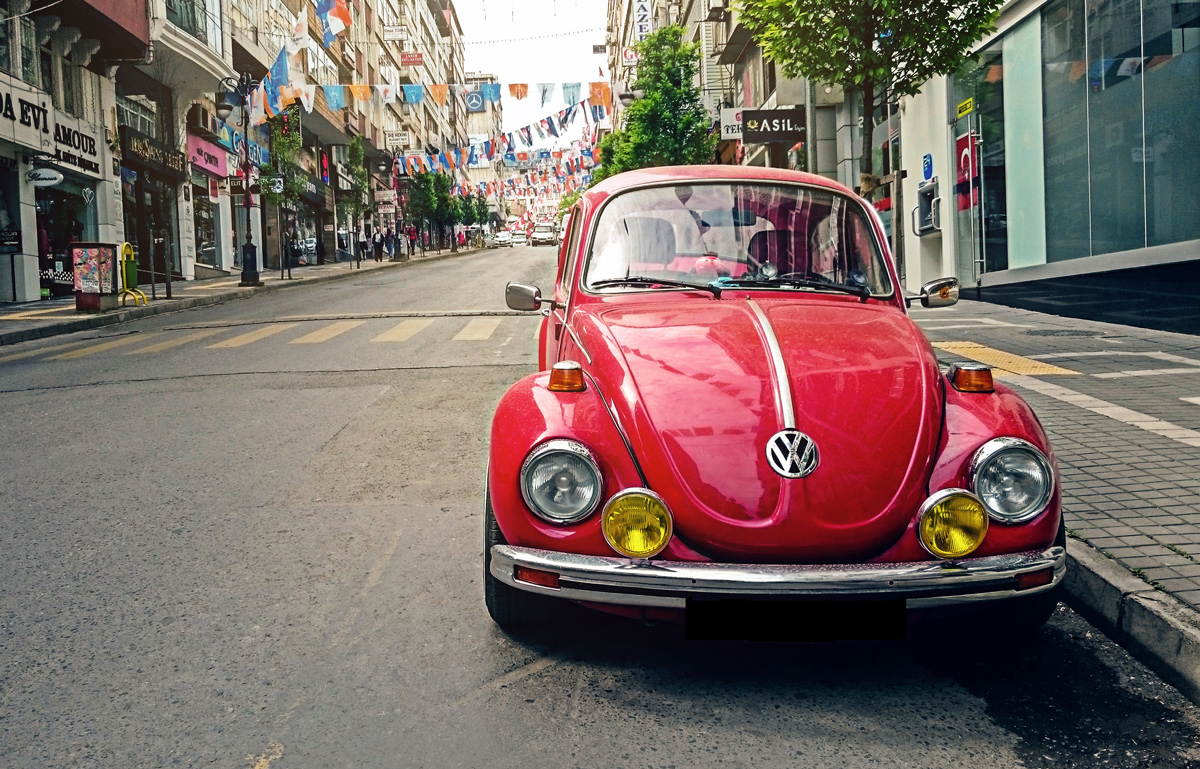 A red VW Beetle parked at the side of a city street