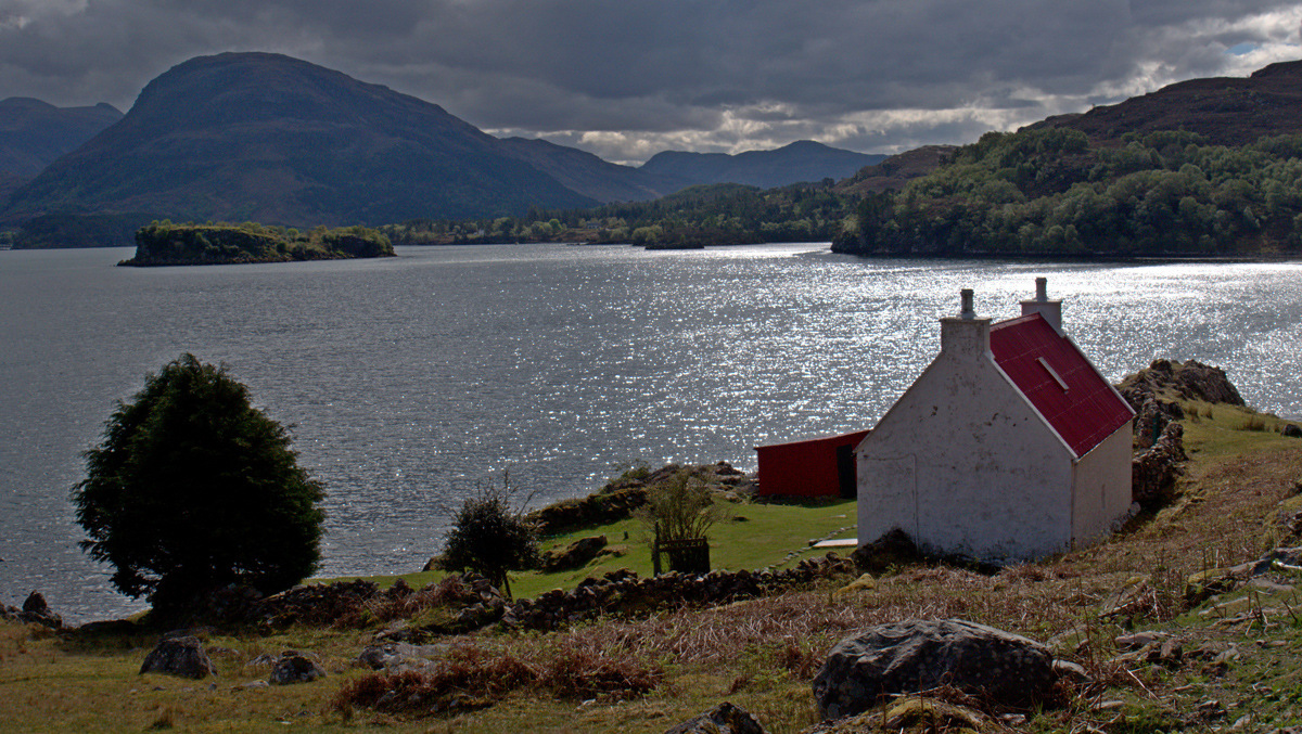 A scenic view across a large loch in Scotland with a white house on the shoreline and mountains in the distance