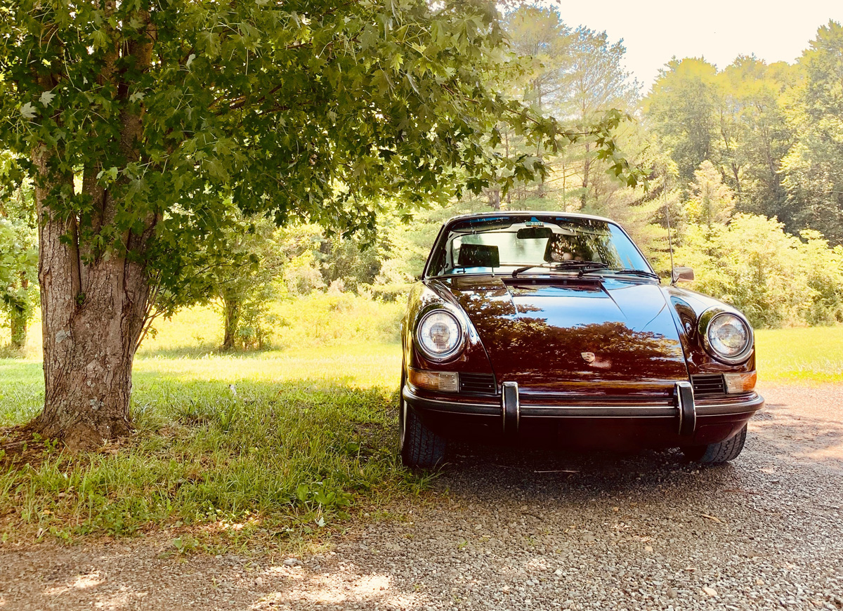 A classic Porsche parked under a tree on a sunny day