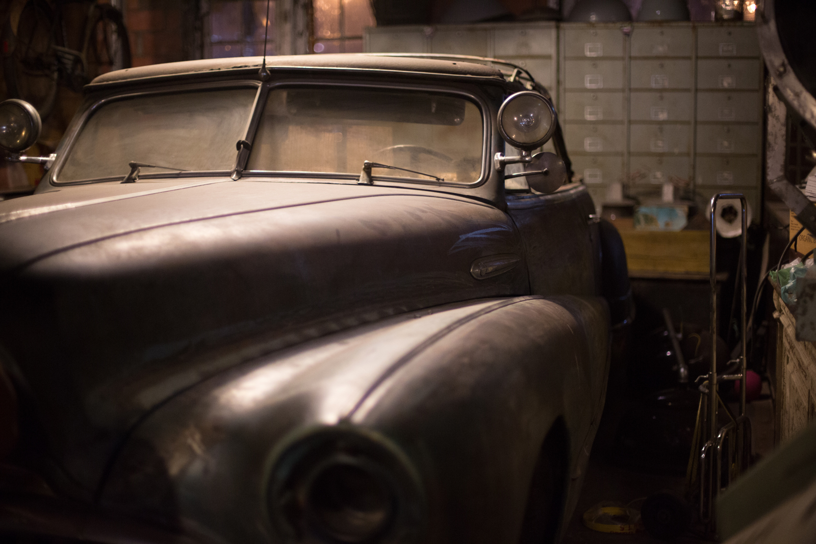 A dusty classic car parked in a garage during restoration