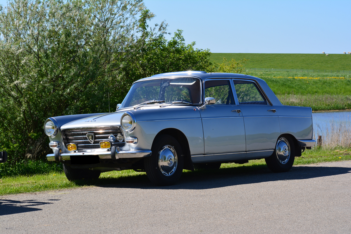 A silver Peugeot 404 parked at the side of a road next to a lake in a country side area on a sunny day