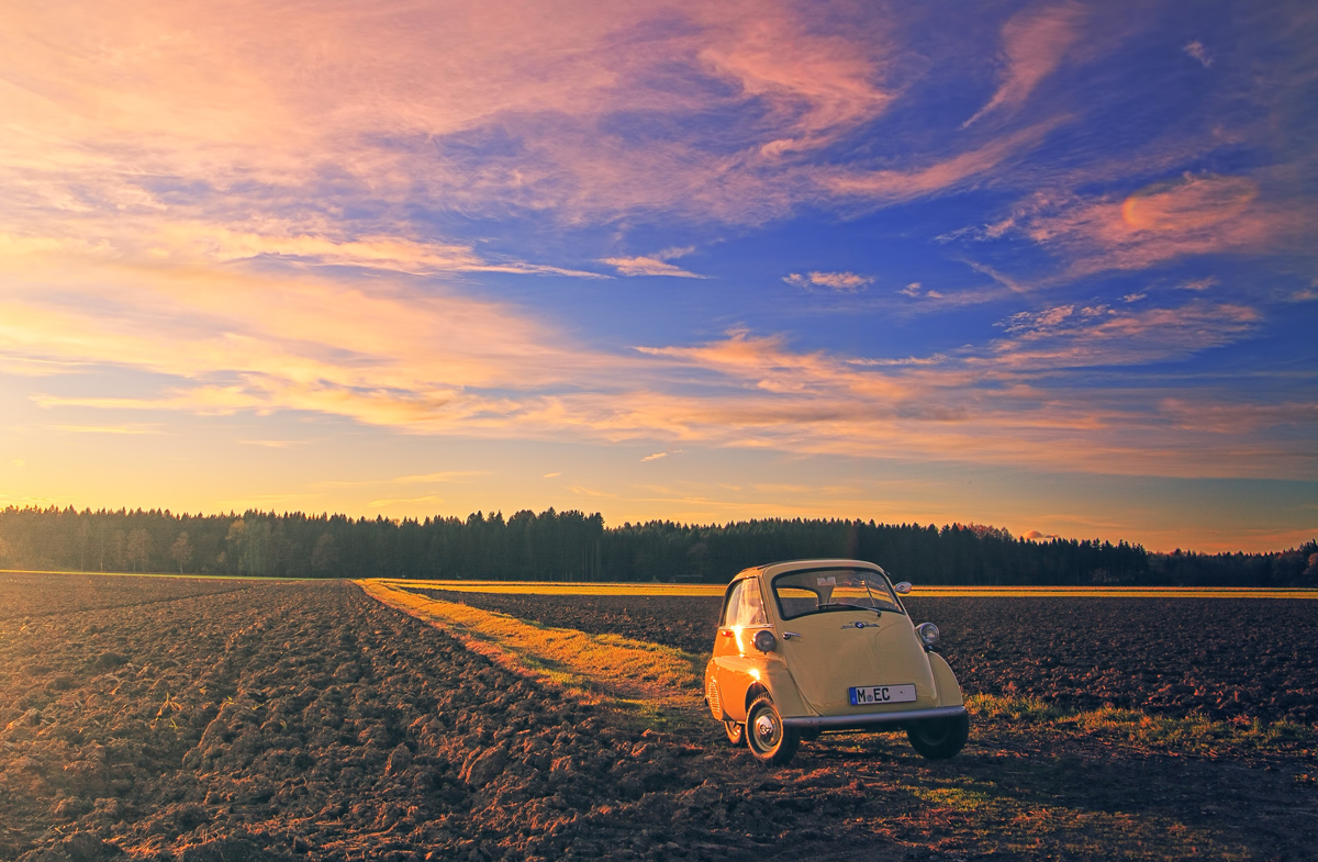 An Isetta bubble car parked on a grass track between ploughed fields at sunset
