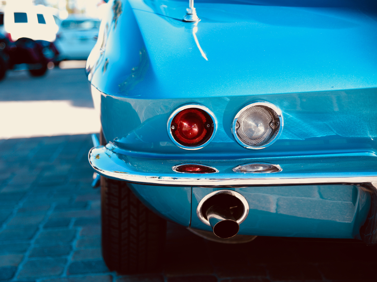 The rear near side corner of a classic teal car with the exhaust poking out