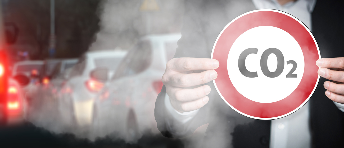 A man in a suit holding up a co2 warning sign in-front of a line of traffic