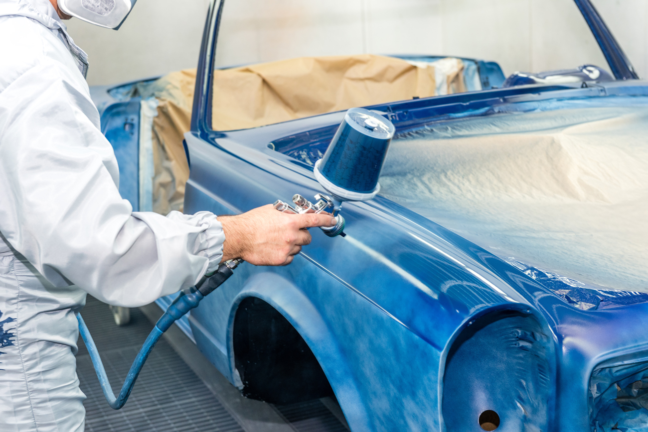 A man in protective clothing and a mask professionally spray painting a classic car shell