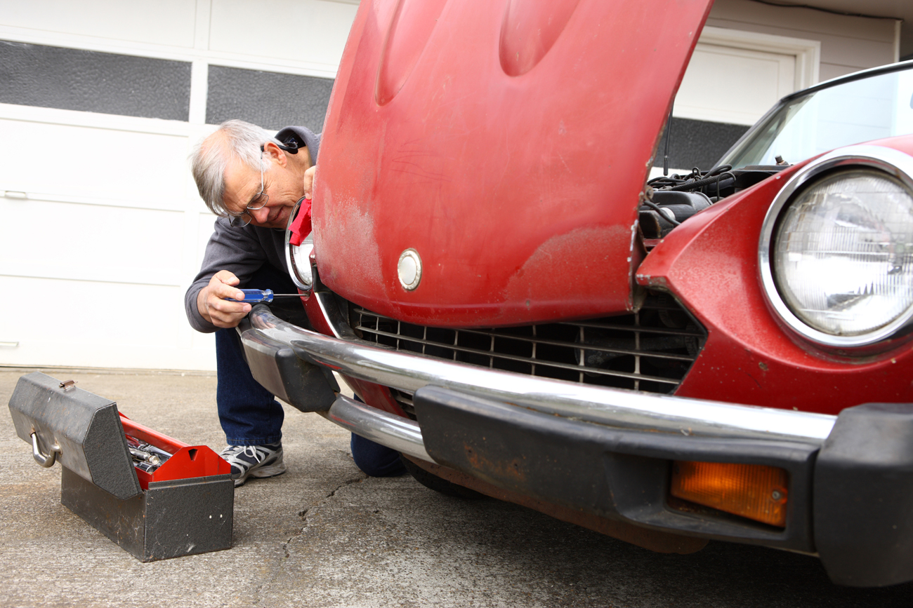 A man using tools to work on restoring his classic car