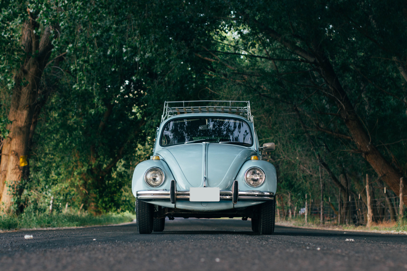 A blue VW Beetle parked in the middle of a road with rows of trees either side