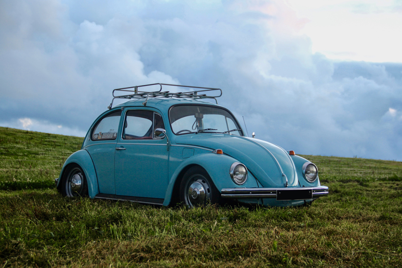 A blue classic VW Beetle with a roof rack parked on a grassy hill against a cloudy sky